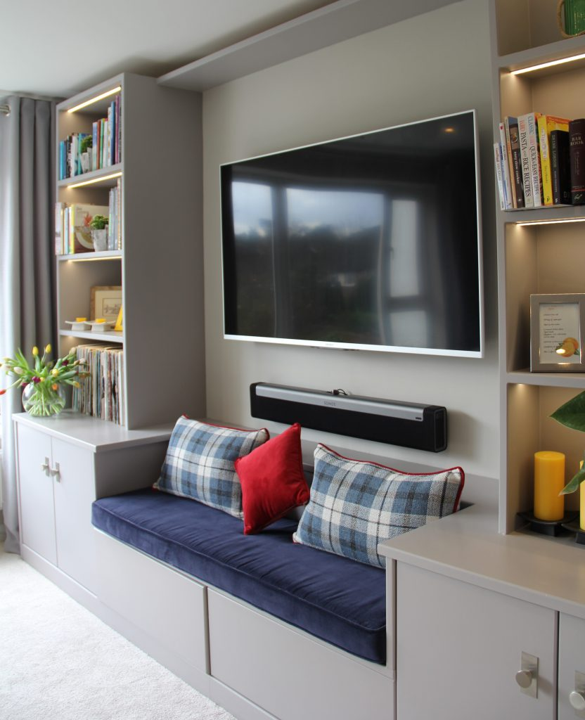 The finised TV unit provides opena and closed storage,additional seating, lit display shleves and concelaed wiring for the TV.